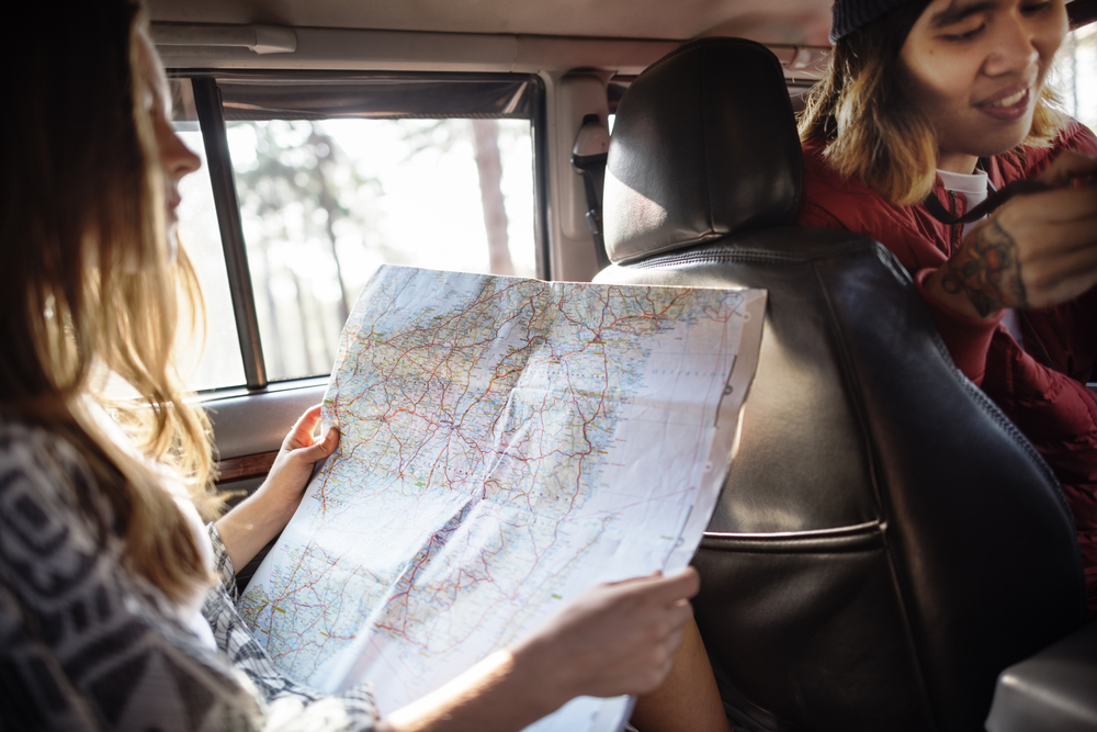 Picture shows woman holding a map inside the car
